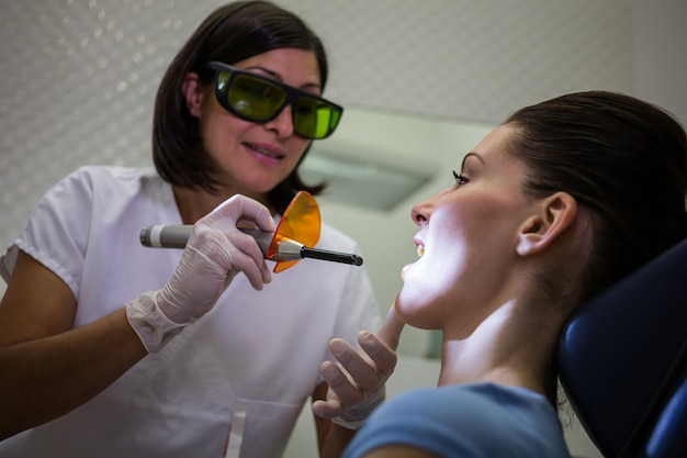 Dentiste examinant les dents des patients avec une lampe à polymériser dentaire