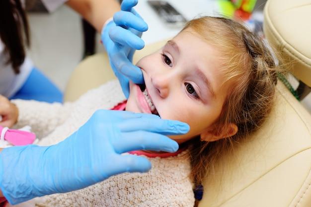 Le dentiste examine les dents d'un enfant dans un fauteuil dentaire.