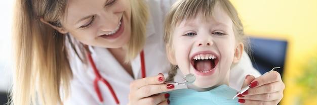 Le dentiste examine les dents d'une fille souriante. traitement dentaire sans concept de douleur