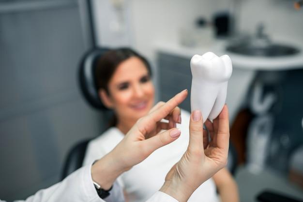 Dentiste expliquant la procédure à un patient.
