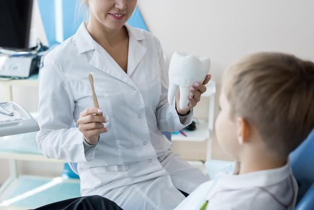 Dentiste expliquant les soins dentaires à l'enfant