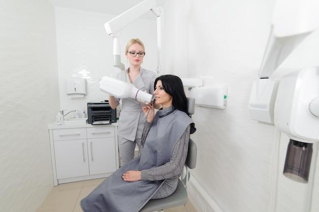 Dentiste faire une image radiographique de la mâchoire pour femme en clinique dentaire