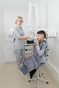 Dentiste faire une image radiographique de la mâchoire pour petit garçon dans une clinique dentaire