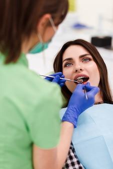 Le dentiste fait un examen oral. jolie femme patiente est venue au rendez-vous chez le dentiste