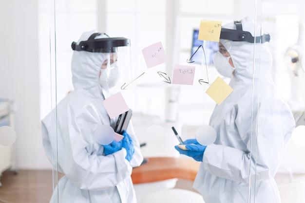 Dentiste fatigué discutant du diagnostic du patient portant un costume ppe. équipe médicale du bureau de stomatologie portant une combinaison dans un cabinet dentaire écrivant des idées sur des notes autocollantes.
