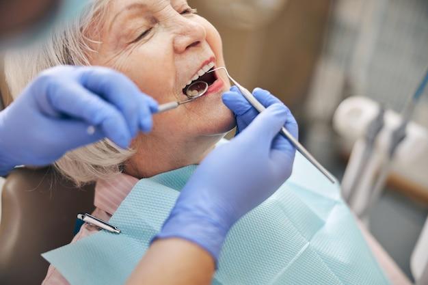 Dentiste féminin examinant les dents d'une charmante miss adulte avec un miroir buccal et une vérification de la sonde