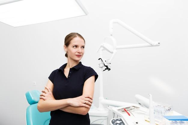 Dentiste féminine confiante se dresse au milieu du bureau blanc