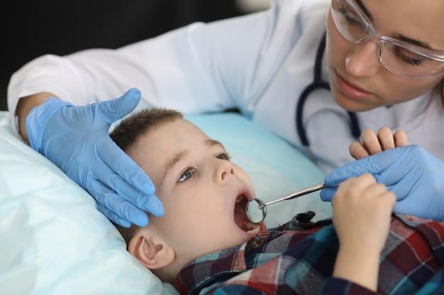 Dentiste femme examine les dents de l'enfant avec des outils métalliques