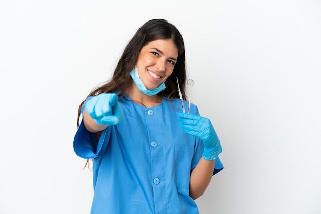 Dentiste femme tenant des outils sur fond blanc isolé pointant vers l'avant avec une expression heureuse