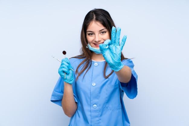 Dentiste femme tenant des outils sur le mur bleu montrant un signe ok avec les doigts