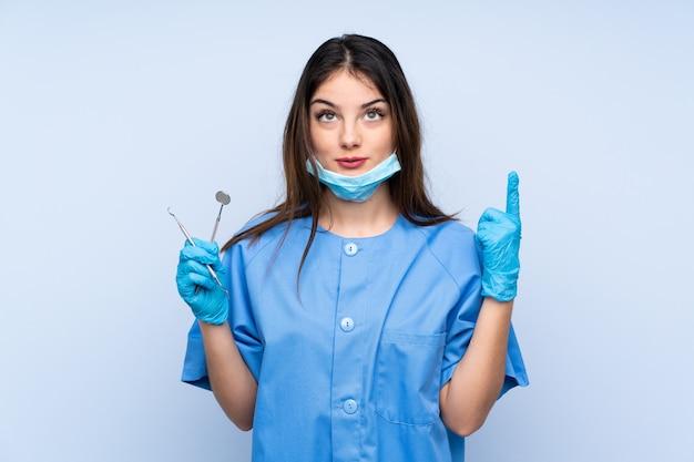 Dentiste femme tenant des outils sur le mur bleu pointant avec l'index une excellente idée