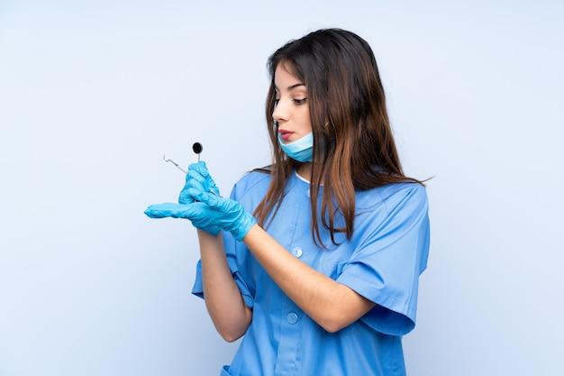 Dentiste femme tenant des outils sur le mur bleu tenant copyspace imaginaire sur la paume