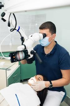 Dentiste en gants en latex examinant les dents du patient en clinique. patient couché avec sa bouche ouverte dans le bureau du dentiste. stomatologue effectuant un examen à l'aide d'un microscope