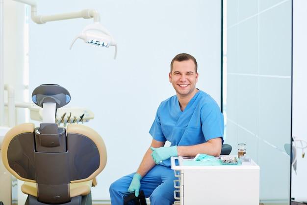 Dentiste homme souriant assis au bureau