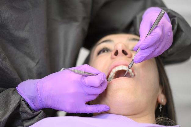 Dentiste hygiéniste faisant le nettoyage hygiénique bucco-dentaire en dentisterie pour jeune femme.