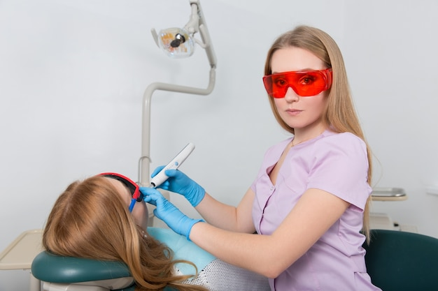 Dentiste avec des lunettes rouges et un dispositif pour les obturations dentaires traite le patient qui est assis dans le fauteuil
