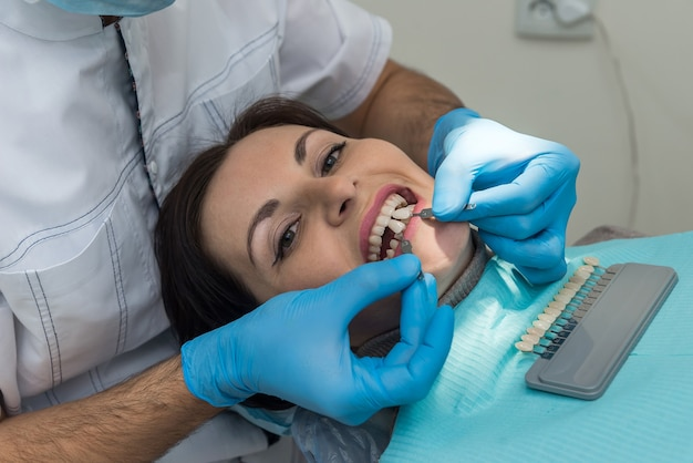 Dentiste mains avec des échantillons de dents par rapport au patient