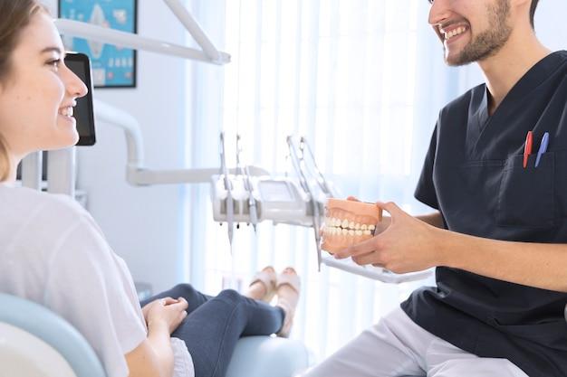 Dentiste mâle expliquant patient tenant modèle de dents en clinique