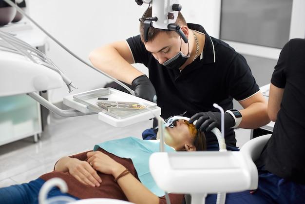 Dentiste mâle en uniforme noir fixant les dents de la jeune fille avec des instruments dentaires