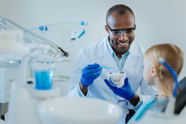 Dentiste masculin agréable optimiste tenant un modèle dentaire et une brosse à dents et disant quelques conseils de soins des dents à son petit patient