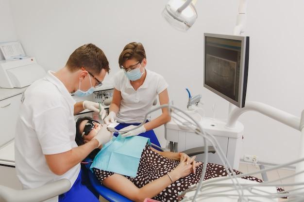 Le dentiste masculin avec une assistante aide à traiter les dents d'une patiente dans une clinique au bureau