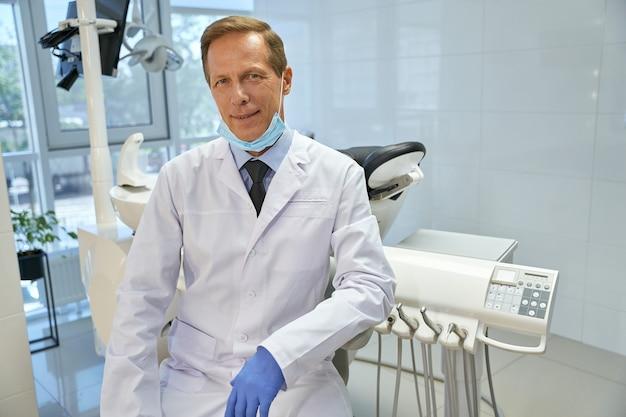 Dentiste masculin calme se tenant dans son bureau près de la perceuse dentaire