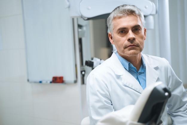 Un dentiste masculin en uniforme blanc se tient dans une clinique moderne et attend un rendez-vous avec les patients.