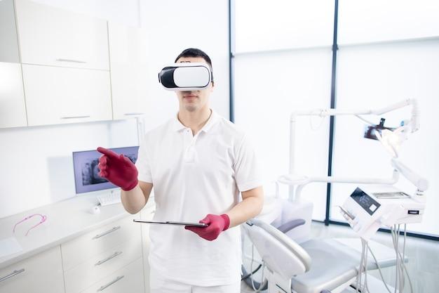 Un dentiste masculin en uniforme se tient dans le bureau et vérifie l'image numérique avant la visite du patient.