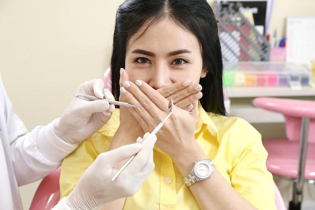 Dentiste avec miroir près de femme