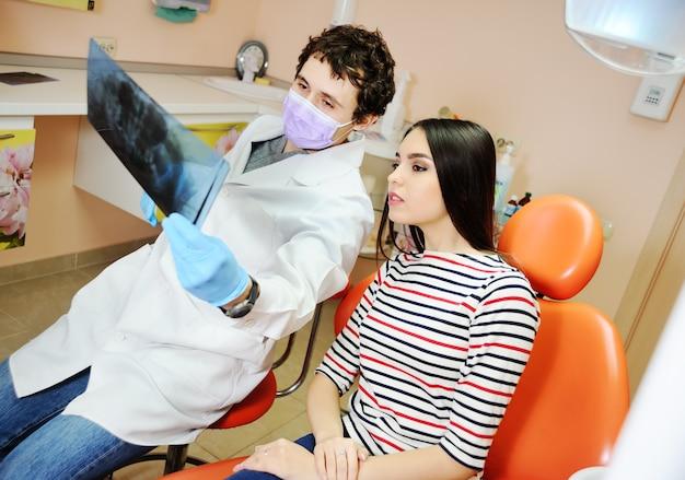 Un dentiste montre une patiente aux rayons x