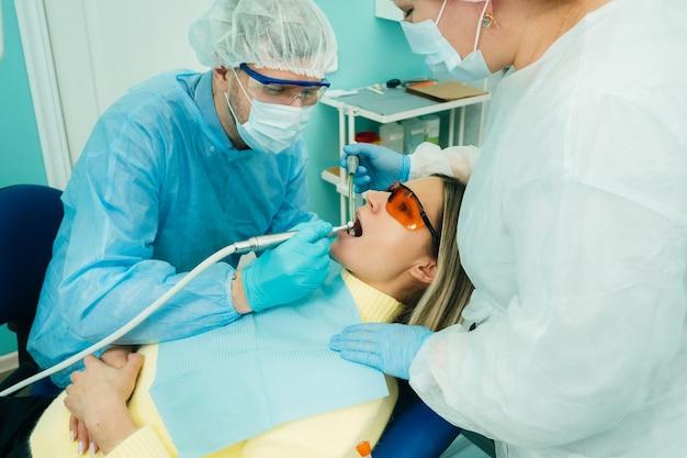 Un dentiste avec des outils dentaires perce les dents d'un patient avec un assistant.