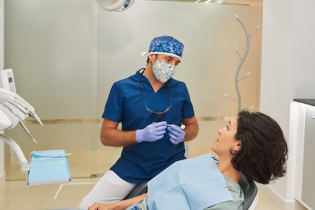 Dentiste parlant à un beau patient dans le cabinet dentaire.