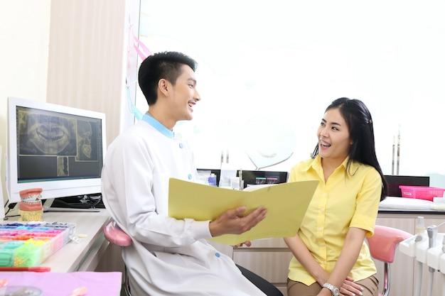 Dentiste parle avec un patient lors d'un examen oral avec un miroir à proximité