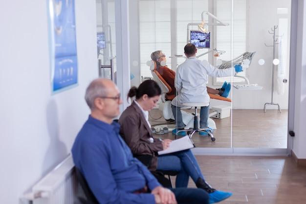 Dentiste avec un patient âgé analysant la radiographie des dents aux rayons x dans un bureau de consultation assis sur une chaise