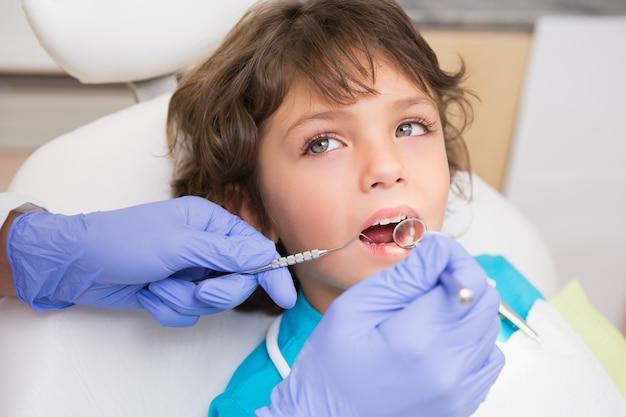 Dentiste pédiatrique examinant les dents d'un petit garçon dans la chaise des dentistes