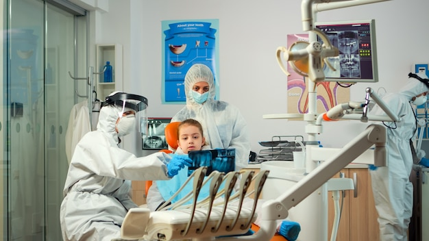 Dentiste pédiatrique portant une combinaison de protection traitant une patiente dans une nouvelle unité stomatologique normale montrant une radiographie des dents. équipe médicale portant une combinaison de protection faciale, un masque, des gants, expliquant la radiographie
