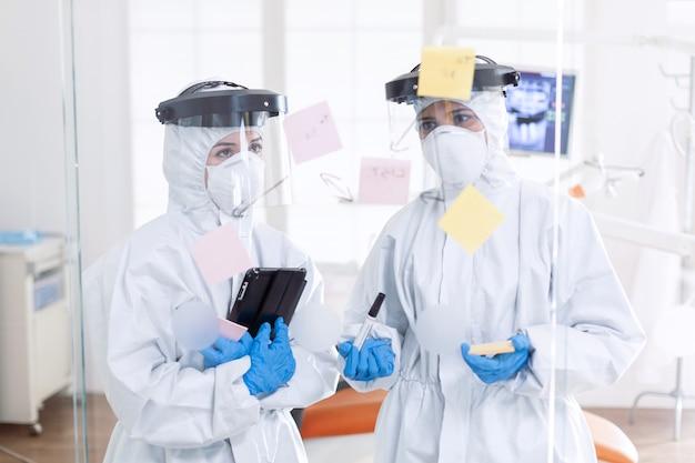 Dentiste pendant le coronavirus portant un costume ppe planant le traitement du patient. équipe médicale du bureau de stomatologie portant une combinaison dans un cabinet dentaire écrivant des idées sur des notes autocollantes.