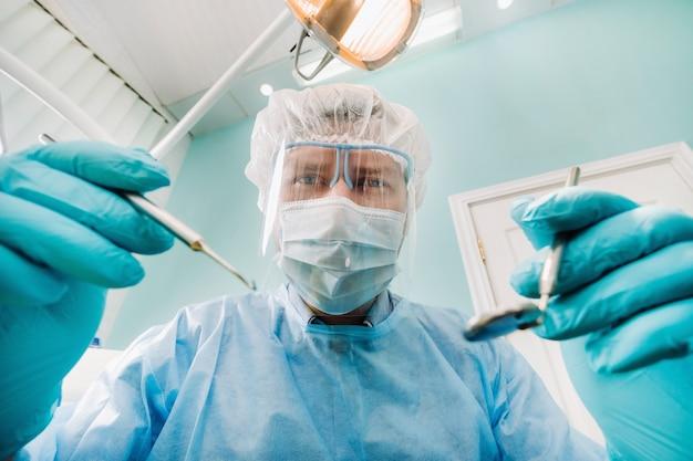 Un dentiste portant un masque de protection est assis à proximité et tient des instruments dans ses mains avant