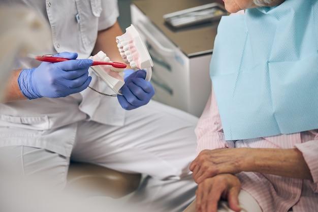Dentiste portant un uniforme blanc tenant un modèle d'implant dentaire pour expliquer le corps de la dent