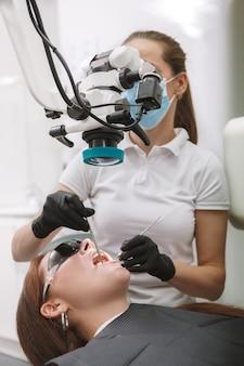 Dentiste professionnel à l'aide d'un microscope dentaire, travaillant dans sa clinique