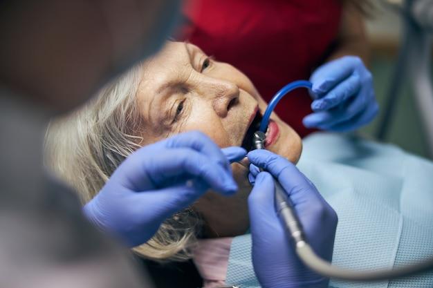 Dentiste professionnel et assistant avec miroir dentaire et perceuse avec pistolet à air comprimé traitant les dents d'une patiente à la clinique dentaire