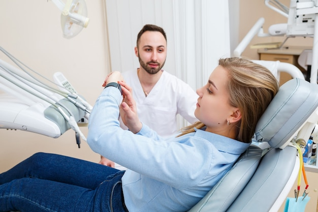 Un dentiste professionnel communique avec une patiente. cabinet dentaire pour l'examen des patients. discussion sur le processus de traitement dentaire.