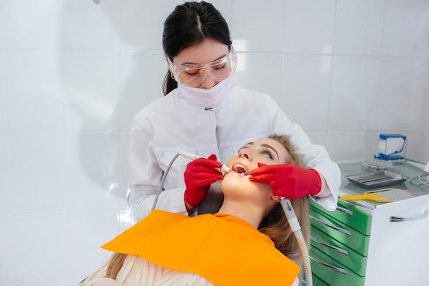 Un dentiste professionnel effectue un traitement et un examen de la cavité buccale du patient en gros plan. dentisterie.