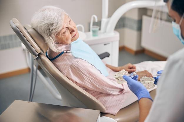 Dentiste professionnel montrant un modèle dentaire à sa patiente âgée tandis que la communication conseille la dentisterie du modèle de la mâchoire