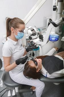 Dentiste professionnel portant un masque médical, à l'aide d'un microscope dentaire sur le patient