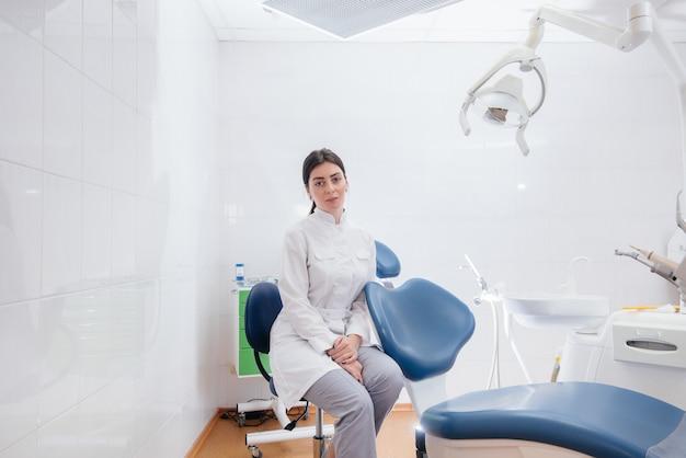 Un dentiste professionnel se tient dans un cabinet dentaire léger moderne