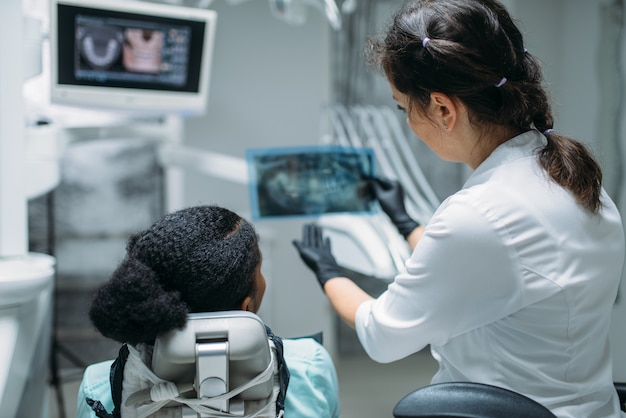 Dentiste à la recherche sur l'image aux rayons x, clinique dentaire