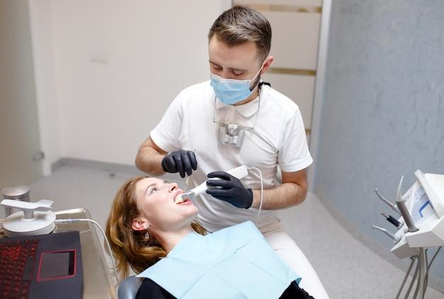Le dentiste scanne les dents du patient avec un scanner 3d.