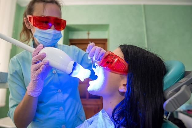 Dentiste se préparant à une procédure de blanchiment avec une patiente