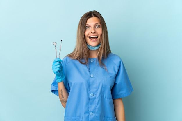 Dentiste slovaque tenant des outils isolés sur fond bleu avec une expression faciale surprise